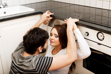 Young couple embracing each-other in the kitchen.