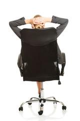 Businesswoman resting on armchair