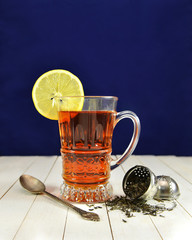 Glass of tea with lemon and strainer on blue background