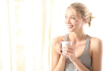 Hübsche Frau mit einer Tasse Kaffee am Morgen