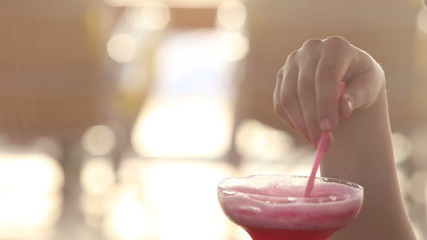 young woman drink red cocktail from the margarita glass and stir