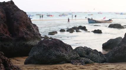 black rock on seashore and sandy beach