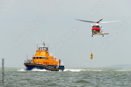 Leinwanddruck Bild Orange sea rescue boat with rescue helicopter