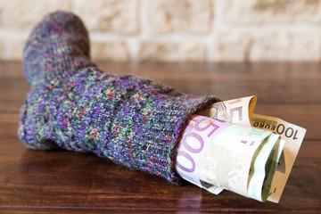 Sparstrumpf mit Euros auf Holztisch