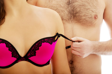 Men taking off woman's bra.