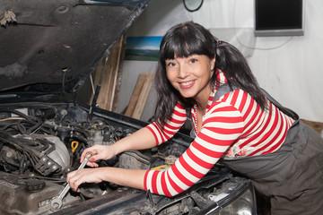 smiling woman repairing the car in the garage