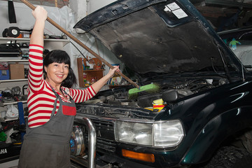 smiling woman washing her car in the garage