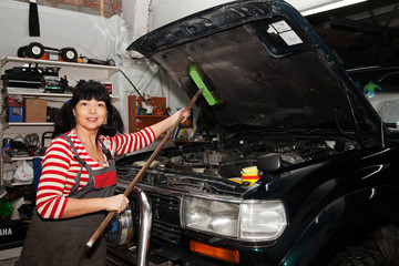 smiling brunette woman washing her car in the garage