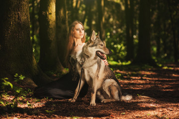 girl with a dog-wolf sitting in the dark forest