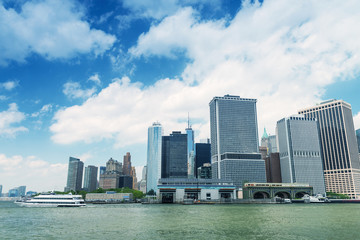 Lower Manhattan skyline with boat crossing river
