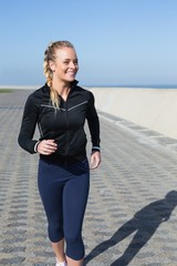 Fit blonde jogging on the pier