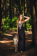 graceful girl posing with a dog in summer forest