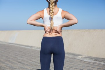 Fit blonde touching her back on the pier