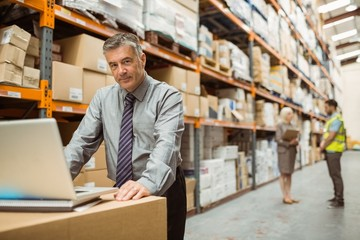 Focused warehouse manager working on laptop