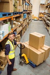 Worker with trolley of boxes smiling at camera