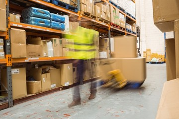 Worker pulling trolley with boxes in a blur