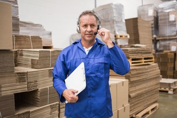 Serious warehouse worker using headset