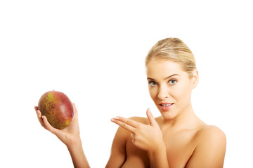 Beautiful nude woman pointing on mango and looking at the camera