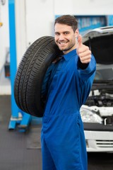 Mechanic holding a tire wheel