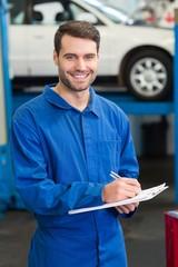 Mechanic writing on a clipboard
