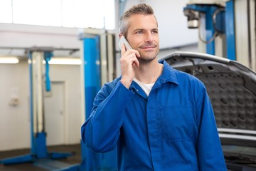 Smiling mechanic on the phone