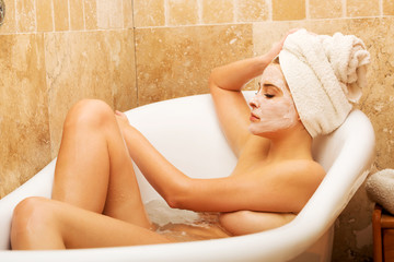 Woman relaxing in bath with face mask