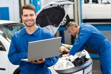 Smiling mechanic using a laptop