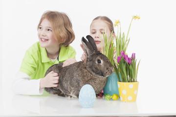 Mädchen und Junge mit Osterhasen, lächelnd