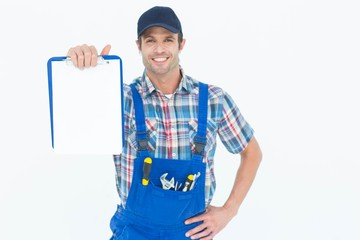 Confident plumber showing blank clipboard