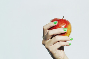 apple in hand with manicure.beauty salon woman.nail design