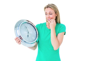 Nervous blonde in casual clothes holding clock