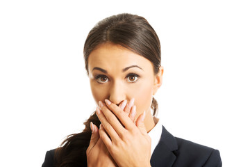 Portrait of shocked businesswoman covering mouth