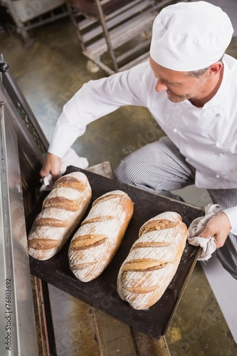 Aluminium Boord Baker taking tray of fresh bread out of oven