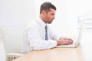 A serious businessman working at desk
