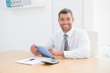 Smiling businessman using his tablet