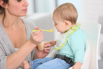 Mother giving fruit sauce to baby boy