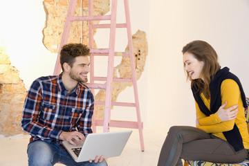 Junger Mann mit Laptop und lachende Frau
