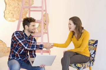 Mann mit Laptop, Frau auf Stuhl, Hände schütteln