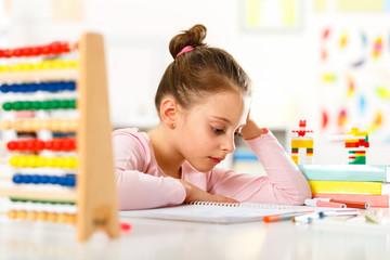 Little girl is doing homework.