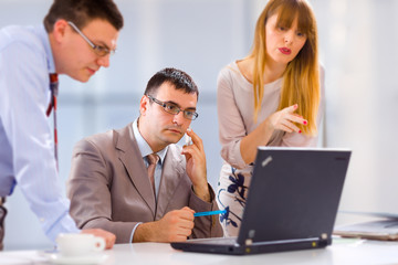 Businesspeople working on laptop in an office