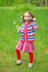 Pretty little girl inflates soap bubbles. Happy childhood