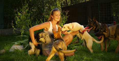 A young beautiful woman with blonde hair is playing with dogs