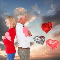 Composite image of couple holding two halves of broken heart