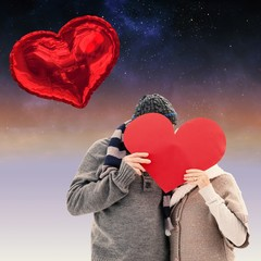 Happy mature couple in winter clothes holding red heart