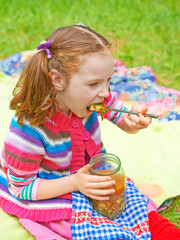 Pretty a little girl eats her soup at a picnic