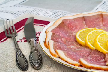 The dish with slices of ham and lemon