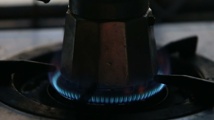 man hand set gas fire at the gas-stove with coffee-pot stand on