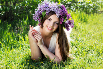 Beautiful girl with wreath of lilac flowers