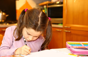 cute little girl writes on her notebook