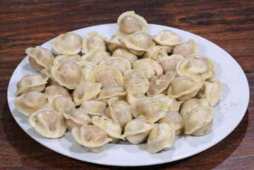 Ready pelmeni submitted with the butter, strewed by ground peppe